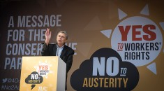 Dave Prentis on stage at the Manchester rally with backdrop reading Yes to workers' rights, No to austerity
