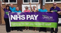 Members standing with banner reading: NHS pay – fighting for fair pay for NHS staff