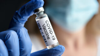 Gloved hand holding vial of COVID-19 vaccine