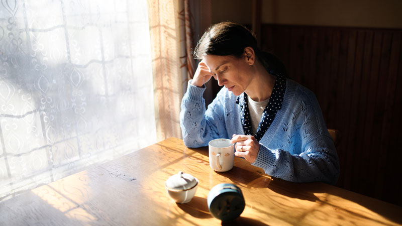 A woman sitting at a dining table looking concerned